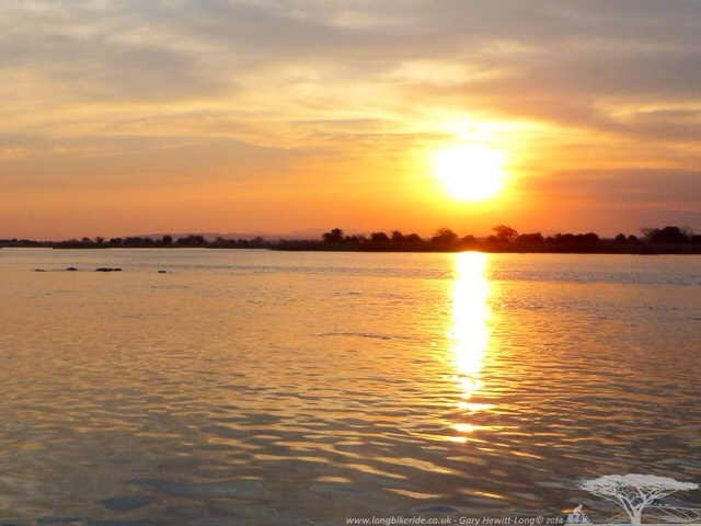The sun going down on the Zambezi River with Hippos in the background